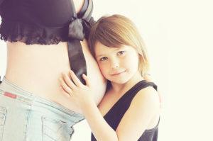 Immagine inerente il mal di denti in gravidanza, raffigurante una bambina che si appoggia alla pancia della mamma