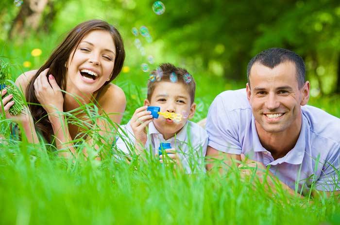 fotografia di una famiglia felice distesa su un prato