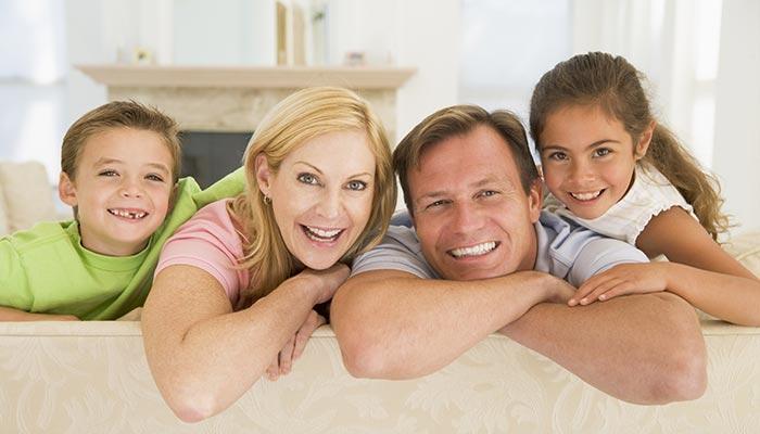 fotografia di una famiglia composta da papà, mamma e bambini sorridenti